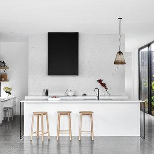 Idee per una cucina ad U design con isola, ante a persiana, ante bianche, paraspruzzi bianco, elettrodomestici bianchi, pavimento grigio e top bianco