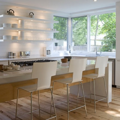 Kitchen - mid-sized modern galley medium tone wood floor kitchen idea in Austin with marble countertops, open cabinets, white cabinets, white backsplash, stainless steel appliances and an island