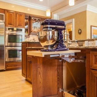 Immagine di una grande cucina classica con lavello sottopiano, ante con bugna sagomata, ante in legno bruno, top in granito, paraspruzzi con piastrelle in pietra, elettrodomestici in acciaio inossidabile, parquet chiaro e isola