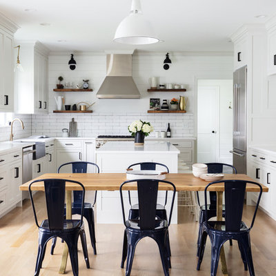 Inspiration for a huge cottage u-shaped light wood floor and brown floor eat-in kitchen remodel in New York with a farmhouse sink, white cabinets, white backsplash, ceramic backsplash, stainless steel appliances, an island, white countertops and shaker cabinets