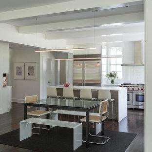 Ispirazione per una grande cucina minimalista con ante lisce, ante bianche, top in superficie solida, paraspruzzi bianco, paraspruzzi in lastra di pietra, elettrodomestici in acciaio inossidabile, parquet scuro, lavello sottopiano, pavimento nero e top bianco