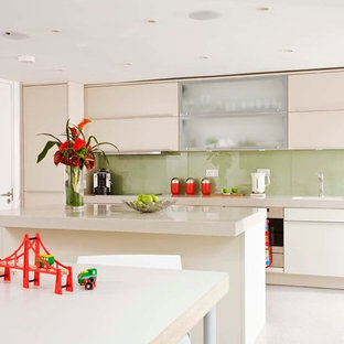 Photo of a medium sized contemporary galley kitchen/diner in Other with a submerged sink, flat-panel cabinets, beige cabinets, green splashback, glass sheet splashback, stainless steel appliances and an island.