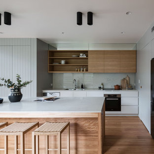 Photo of a large contemporary galley kitchen pantry in Sydney with an undermount sink, flat-panel cabinets, white cabinets, quartz benchtops, white splashback, black appliances, medium hardwood floors, with island and white benchtop.
