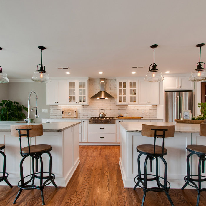 Heres a closer angle of the kitchen only.  Details such as schoolhouse pendants, an industrial faucet and distressed brick subway tile creates a simple yet strong farmhouse statement.