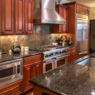 Große Klassische Wohnküche in U-Form mit Unterbauwaschbecken, profilierten Schrankfronten, dunklen Holzschränken, Granit-Arbeitsplatte, bunter Rückwand, Rückwand aus Schiefer, Küchengeräten aus Edelstahl, braunem Holzboden, zwei Kücheninseln, braunem Boden und schwarzer Arbeitsplatte in Sonstige