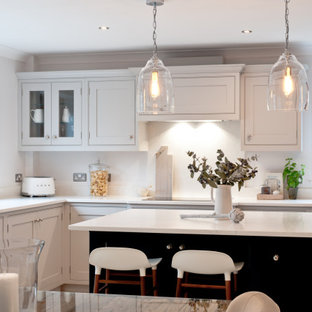 Design ideas for a medium sized traditional l-shaped kitchen/diner in Kent with shaker cabinets, grey cabinets, quartz worktops, white splashback, stainless steel appliances, an island and white worktops.