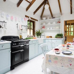 Landhaus Wohnküche ohne Insel in L-Form mit Landhausspüle, Schrankfronten im Shaker-Stil, blauen Schränken, Küchenrückwand in Weiß, schwarzen Elektrogeräten, gebeiztem Holzboden, weißem Boden und weißer Arbeitsplatte in Melbourne