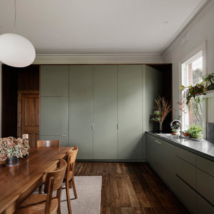 Contemporary l-shaped eat-in kitchen in Melbourne with a double-bowl sink, flat-panel cabinets, green cabinets, panelled appliances, dark hardwood floors, no island, brown floor and black benchtop.