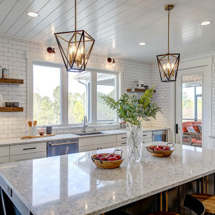Farmhouse enclosed kitchen designs - Enclosed kitchen - farmhouse medium tone wood floor and brown floor enclosed kitchen idea in Grand Rapids with an undermount sink, shaker cabinets, white cabinets, white backsplash, subway tile backsplash, stainless steel appliances and an island
