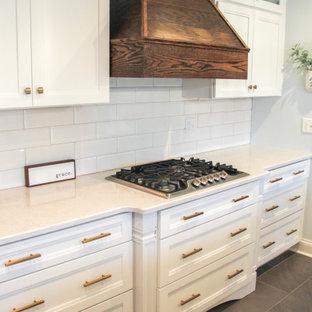 セントルイスのモダンスタイルのおしゃれなアイランドキッチン (アンダーカウンターシンク、白いキャビネット、クオーツストーンカウンター、黄色いキッチンパネル、セラミックタイルのキッチンパネル、セラミックタイルの床、グレーの床、白いキッチンカウンター) の写真