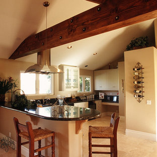 Inspiration for a large arts and crafts u-shaped open plan kitchen in San Diego with white cabinets, granite benchtops, stainless steel appliances, louvered cabinets, a peninsula and limestone floors.