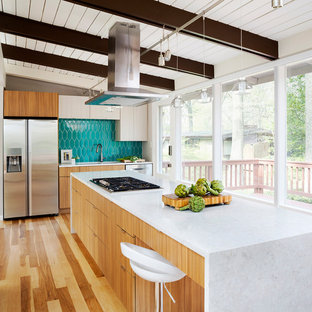 Large midcentury l-shaped kitchen in DC Metro with flat-panel cabinets, medium wood cabinets, blue splashback, stainless steel appliances, medium hardwood floors, with island and brown floor.