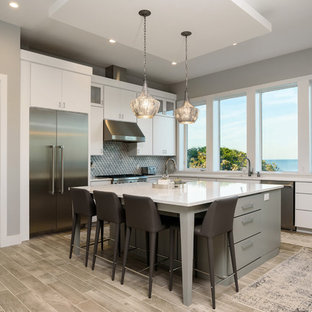 Mid-sized contemporary eat-in kitchen designs - Example of a mid-sized trendy l-shaped ceramic floor and gray floor eat-in kitchen design in Jacksonville with flat-panel cabinets, white cabinets, gray backsplash, limestone backsplash, stainless steel appliances, an island and white countertops