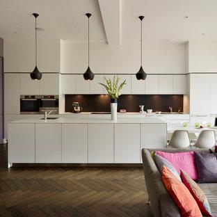 Idéer för att renovera ett funkis kök, med släta luckor, vita skåp, svart stänkskydd och en köksö