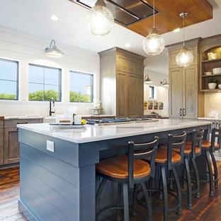 グランドラピッズのカントリー風おしゃれなキッチン (エプロンフロントシンク、シェーカースタイル扉のキャビネット、濃色木目調キャビネット、白いキッチンパネル、サブウェイタイルのキッチンパネル、濃色無垢フローリング、茶色い床、白いキッチンカウンター) の写真