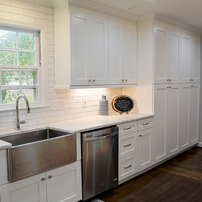 Mid-sized farmhouse l-shaped dark wood floor eat-in kitchen photo in Charlotte with a farmhouse sink, flat-panel cabinets, white cabinets, quartzite countertops, white backsplash, porcelain backsplash, stainless steel appliances and a peninsula