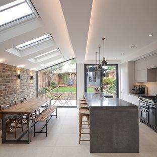 ロンドンの中サイズのコンテンポラリースタイルのおしゃれなキッチン (フラットパネル扉のキャビネット、グレーのキャビネット、コンクリートカウンター、白いキッチンパネル、レンガのキッチンパネル、黒い調理設備、白い床) の写真