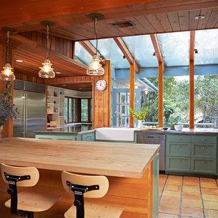 Пример оригинального дизайна: отдельная, п-образная кухня в стиле рустика с полом из терракотовой плитки, раковиной в стиле кантри, фасадами в стиле шейкер, зелеными фасадами, столешницей из нержавеющей стали, техникой из нержавеющей стали, полуостровом и оранжевым полом