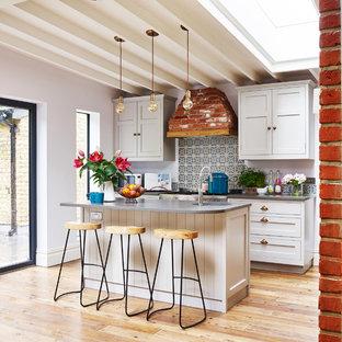 Idee per una cucina parallela design con lavello sottopiano, ante in stile shaker, ante bianche, paraspruzzi multicolore, elettrodomestici in acciaio inossidabile, pavimento in legno massello medio, isola e pavimento marrone