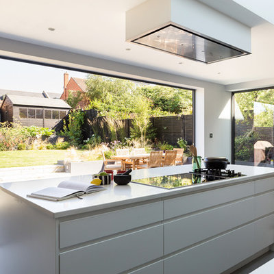 Kitchen - contemporary concrete floor kitchen idea in London with flat-panel cabinets, white cabinets and an island