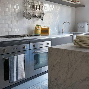 Свежая идея для дизайна: параллельная кухня среднего размера в стиле неоклассика (современная классика) с обеденным столом, раковиной в стиле кантри, плоскими фасадами, серыми фасадами, столешницей из нержавеющей стали, белым фартуком, фартуком из керамической плитки, техникой из нержавеющей стали, полом из керамической плитки и островом - отличное фото интерьера