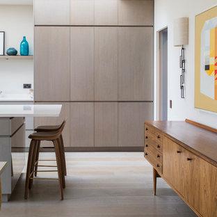 Zweizeilige, Große Mid-Century Wohnküche mit flächenbündigen Schrankfronten, hellen Holzschränken, Küchenrückwand in Weiß, Halbinsel und weißem Boden in London