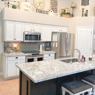 フェニックスのサンタフェスタイルのおしゃれなキッチン (シングルシンク、白いキャビネット、御影石カウンター、グレーのキッチンパネル、ガラスタイルのキッチンパネル、シルバーの調理設備の、セラミックタイルの床、ベージュの床、グレーのキッチンカウンター) の写真