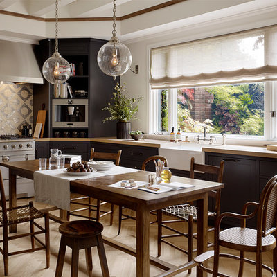 Inspiration for a transitional eat-in kitchen remodel in San Francisco with a farmhouse sink, recessed-panel cabinets, dark wood cabinets, metallic backsplash and stainless steel appliances