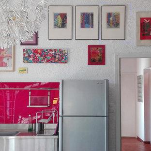 Eklektische Wohnküche in L-Form mit Küchenrückwand in Rosa, Glasrückwand, Küchengeräten aus Edelstahl, Doppelwaschbecken und Edelstahl-Arbeitsplatte
