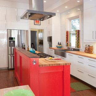Zweizeilige Moderne Wohnküche mit Landhausspüle, flächenbündigen Schrankfronten, weißen Schränken, Arbeitsplatte aus Holz, Küchenrückwand in Weiß, dunklem Holzboden und Kücheninsel in Sonstige