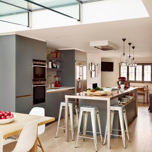 Large contemporary open plan kitchen in London with a submerged sink, flat-panel cabinets, grey cabinets, stainless steel worktops, grey splashback, ceramic splashback, stainless steel appliances, light hardwood flooring and an island.