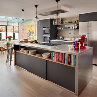 Inspiration for a large contemporary open plan kitchen in London with a submerged sink, flat-panel cabinets, grey cabinets, stainless steel worktops, grey splashback, ceramic splashback, stainless steel appliances, light hardwood flooring and an island.