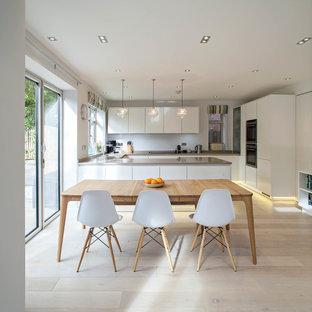 Ispirazione per una grande cucina nordica con ante lisce, ante bianche, parquet chiaro e penisola