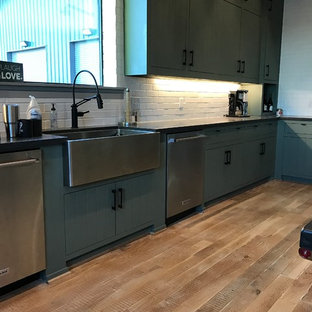 This is an example of an expansive industrial u-shaped open plan kitchen in Dallas with a farmhouse sink, green cabinets, concrete benchtops, white splashback, brick splashback, stainless steel appliances, light hardwood floors, with island, shaker cabinets and beige floor.