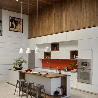 Offene, Einzeilige, Große Moderne Küche mit flächenbündigen Schrankfronten, weißen Schränken, Arbeitsplatte aus Holz, Küchenrückwand in Rot, Küchengeräten aus Edelstahl, Betonboden, Kücheninsel, Glasrückwand und Unterbauwaschbecken in Boston