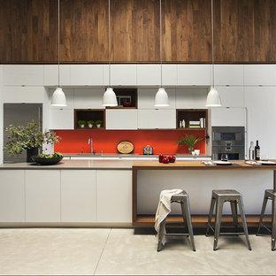 Ejemplo de cocina lineal, contemporánea, abierta, con armarios con paneles lisos, puertas de armario blancas, encimera de madera, electrodomésticos de acero inoxidable, una isla y salpicadero naranja