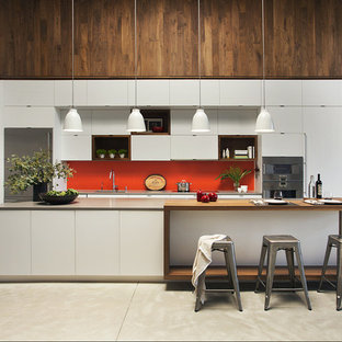 Contemporary open concept kitchen ideas - Open concept kitchen - contemporary single-wall open concept kitchen idea in Boston with flat-panel cabinets, white cabinets, wood countertops, stainless steel appliances, an island and orange backsplash