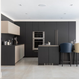 Inspiration for a large contemporary l-shaped kitchen/diner in Hertfordshire with an integrated sink, quartz worktops, black splashback, porcelain flooring, an island, beige floors, black worktops, flat-panel cabinets, black cabinets and stainless steel appliances.