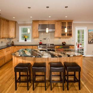 Idéer för ett mellanstort klassiskt kök, med en undermonterad diskho, skåp i mellenmörkt trä, granitbänkskiva, beige stänkskydd, stänkskydd i keramik, rostfria vitvaror, mellanmörkt trägolv och en köksö
