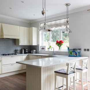 Design ideas for a medium sized classic u-shaped open plan kitchen in London with a submerged sink, shaker cabinets, beige cabinets, granite worktops, grey splashback, porcelain splashback, stainless steel appliances, porcelain flooring, a breakfast bar and brown floors.