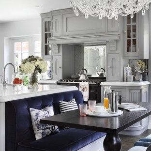 Large classic kitchen/diner in London with grey cabinets, marble worktops, metallic splashback, mirror splashback, dark hardwood flooring and an island.