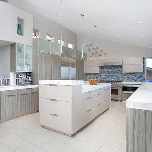 Immagine di una grande cucina design con lavello sottopiano, ante lisce, ante grigie, top piastrellato, paraspruzzi blu, paraspruzzi con piastrelle di vetro, elettrodomestici in acciaio inossidabile, pavimento in gres porcellanato e isola