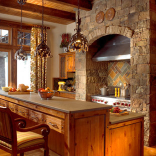 Design ideas for a country kitchen in Denver with medium wood cabinets, stainless steel appliances and slate splashback.