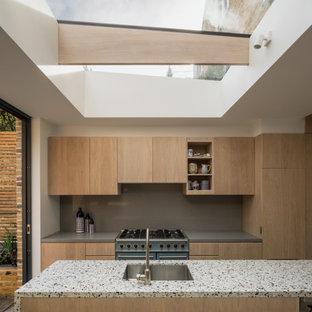 Einzeilige, Mittelgroße Moderne Wohnküche mit Unterbauwaschbecken, flächenbündigen Schrankfronten, hellbraunen Holzschränken, Arbeitsplatte aus Terrazzo, Küchenrückwand in Grau, Kalk-Rückwand, bunten Elektrogeräten, Betonboden, Kücheninsel, grauem Boden und bunter Arbeitsplatte in Essex
