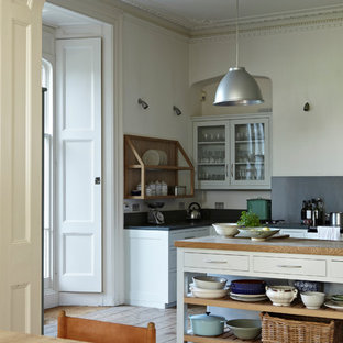 Large country galley kitchen/diner in Dorset with flat-panel cabinets, beige cabinets, wood worktops, blue splashback, stainless steel appliances, light hardwood flooring and an island.