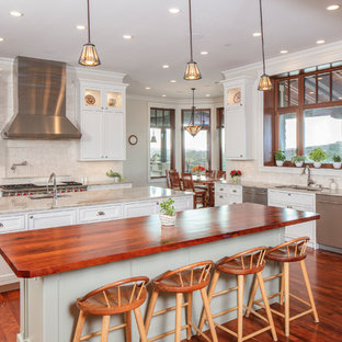 Traditional kitchen remodeling - Elegant medium tone wood floor kitchen photo in Austin with an undermount sink, shaker cabinets, white cabinets, beige backsplash, stainless steel appliances, two islands and beige countertops