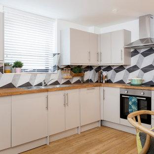 ハンプシャーの小さいコンテンポラリースタイルのおしゃれなキッチン (フラットパネル扉のキャビネット、グレーのキャビネット、木材カウンター、セメントタイルのキッチンパネル、シルバーの調理設備、クッションフロア、ダブルシンク、グレーのキッチンパネル、アイランドなし、ベージュの床、茶色いキッチンカウンター) の写真