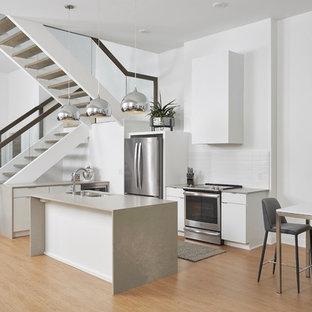 ミネアポリスのコンテンポラリースタイルのおしゃれなキッチン (ダブルシンク、フラットパネル扉のキャビネット、白いキャビネット、白いキッチンパネル、シルバーの調理設備の、クッションフロア、ベージュのキッチンカウンター) の写真