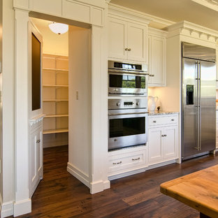 This is an example of a traditional kitchen in Other with stainless steel appliances and subway tile splashback.