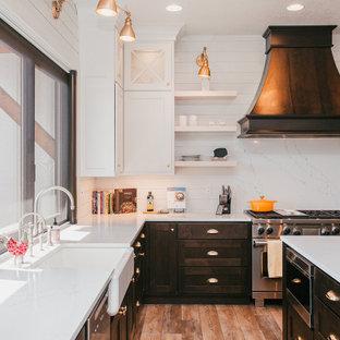 Expansive country u-shaped kitchen in Portland with a farmhouse sink, shaker cabinets, dark wood cabinets, quartz benchtops, white splashback, shiplap splashback, medium hardwood floors, with island and brown floor.